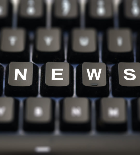 Online news, journalism concept. News word written on keypad. Black keys with white letters message for press articles on pc keyboard. Blur buttons background.